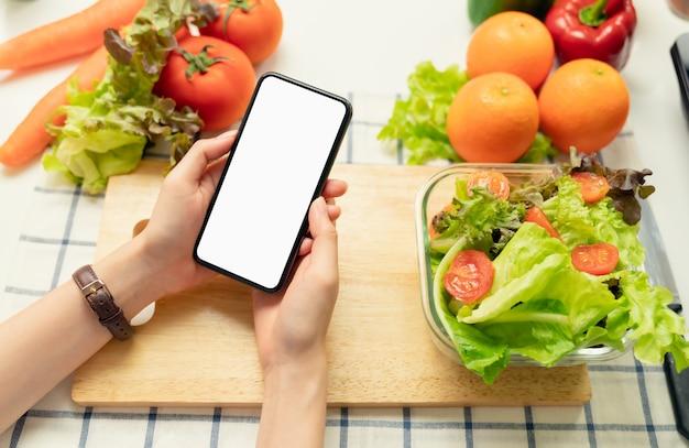 Main de femme tenant un écran vide de smartphone et un saladier avec tomate et divers légumes à feuilles vertes sur la table à la maison, prenez votre publicité.