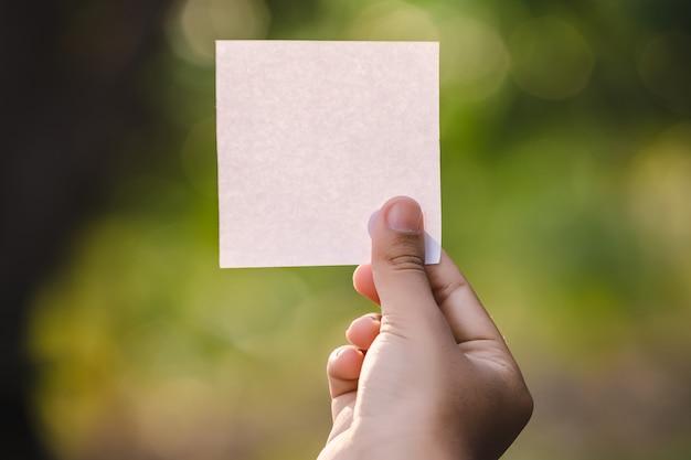 Main de femme tenant une feuille de papier vierge