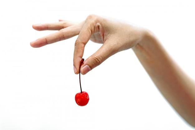 Main de femme tenant un fruit de cerises rouges isolé sur fond blanc