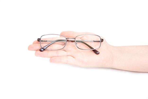 Main de femme tenant glasse sur fond blanc. lunettes à la main