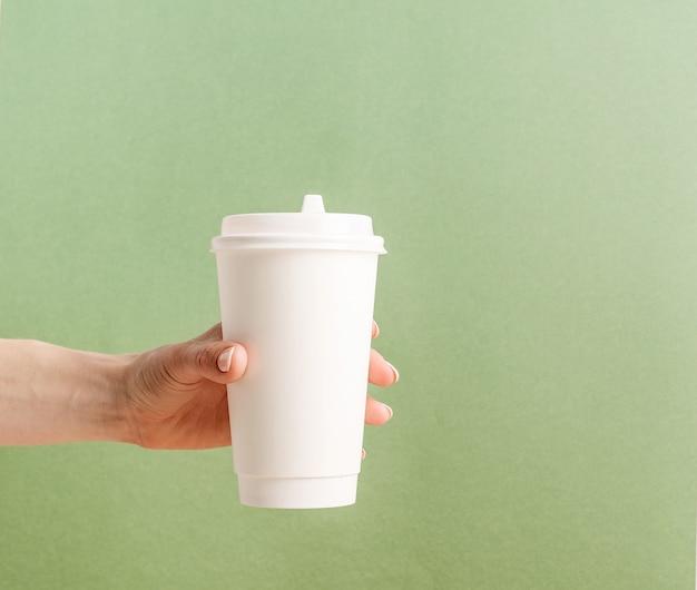 Main de femme tenant une grande tasse de café en papier à emporter blanc maquette sur fond vert