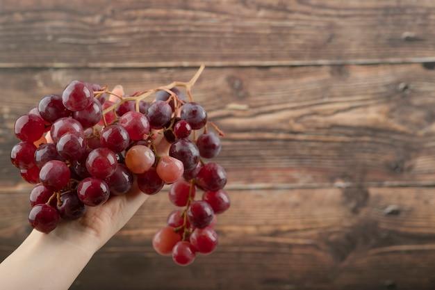 Main de femme tenant une grappe de raisin rouge sur une table en bois.