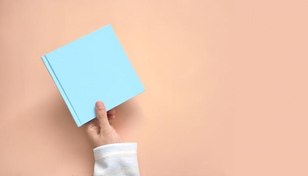 Main de femme tenant un livre sur fond de couleur