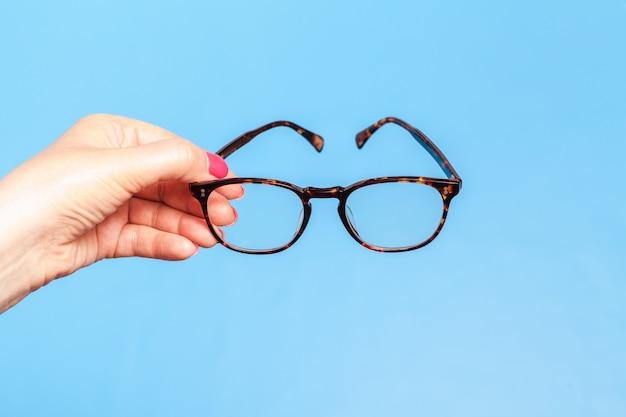 Main de femme tenant des lunettes sur fond bleu