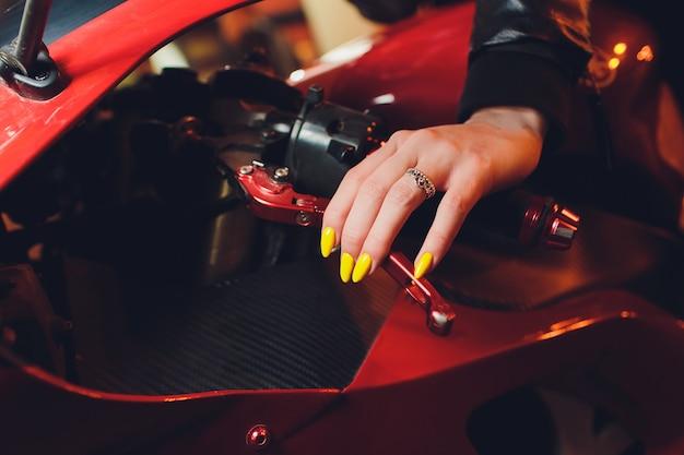 Main de femme tenant manucure volant jaune moto.