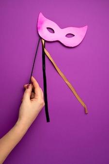 Main de femme tenant un masque de mardi gras ou de carnaval festif et coloré sur un mur violet. mise à plat, vue de dessus