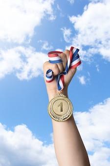 Main de femme tenant la médaille d'or contre sky.award et victoire concept.copy space