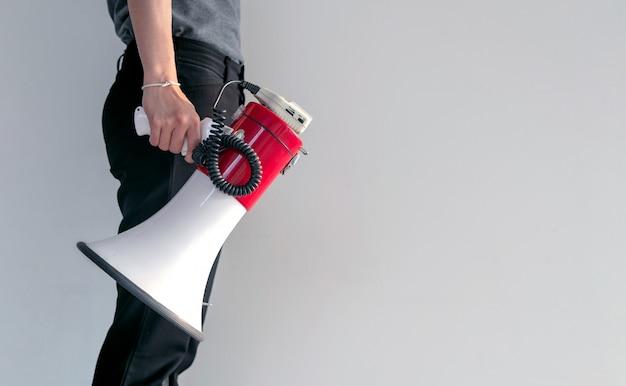 Main de femme tenant un mégaphone sur fond de mur de briques blanches