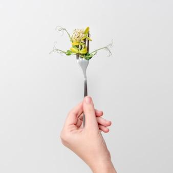 Main de femme tenant des micro verts sur la fourche.