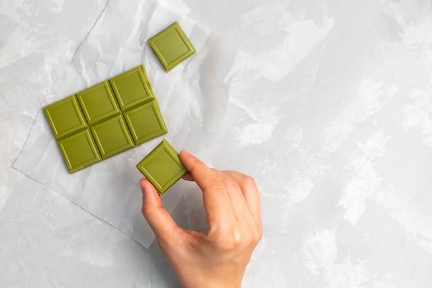 Main de femme tenant un morceau de chocolat au thé vert matcha