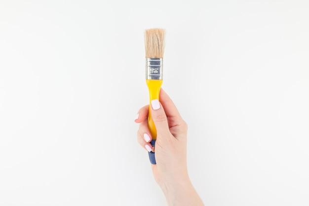 Main de femme tenant un nouveau pinceau isolé