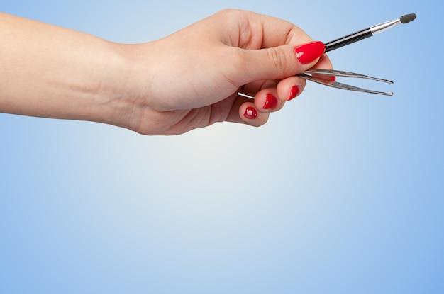 Main de femme tenant un outil cosmétique isolé