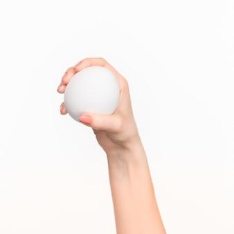 Main de femme tenant un ovale en polystyrène blanc vierge sur le fond blanc avec ombre droite