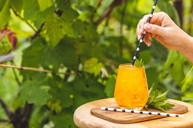 Main de femme tenant de la paille sur une boisson orange avec de la glace sur fond de jardin ensoleillé d'été