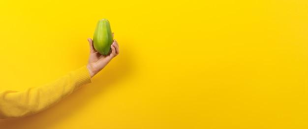 Main de femme tenant la papaye verte sur fond jaune, concept d'aliments sains