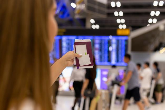 Main de femme tenant passeport et carte d'embarquement à l'aéroport en arrière-plan flou.
