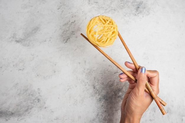 Main de femme tenant des pâtes tagliatelles crues avec des baguettes en bois sur fond blanc.