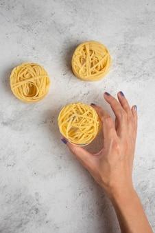 Main de femme tenant des pâtes tagliatelles crues sur une surface blanche.