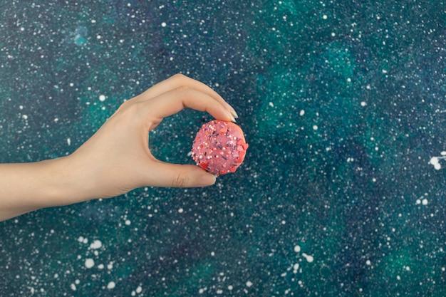 Main de femme tenant un petit beignet rose.