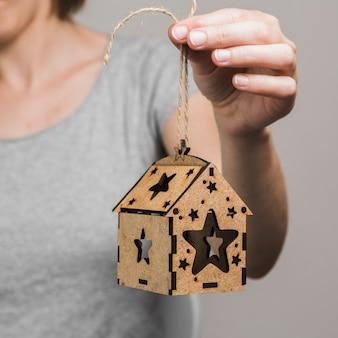 Main de femme tenant une petite maison brune
