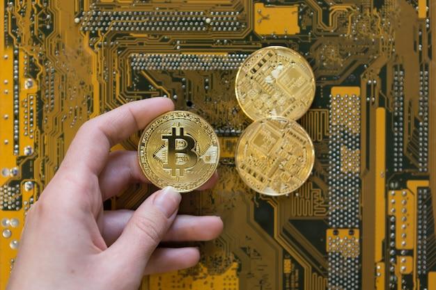 Main de femme tenant une pièce de monnaie bitcoin dorée sur une carte d'ordinateur, une carte graphique et un fond minier, vue de dessus à plat