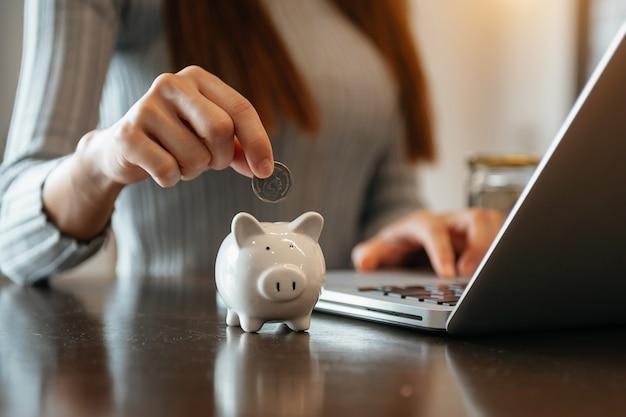 Main de femme tenant une pièce avec une tirelire cochon. concept de comptes d'épargne et financiers