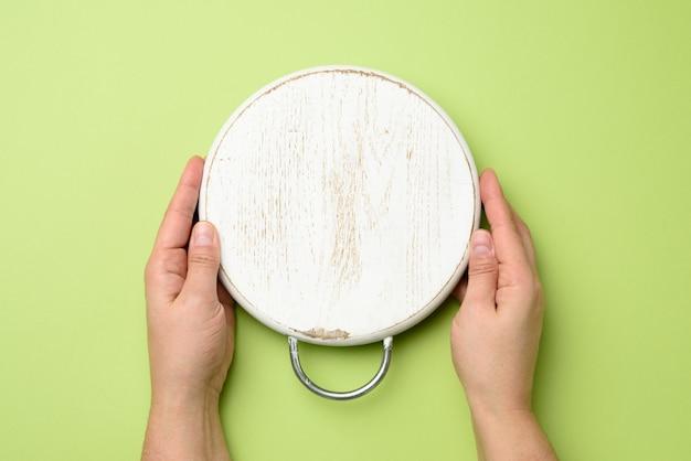 Main de femme tenant une planche de bois ronde vide blanche à la main, vert, vue de dessus