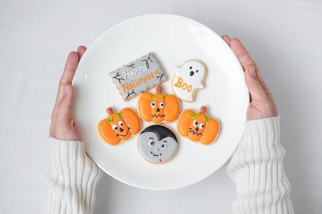 Main de femme tenant la plaque de drôles de biscuits d'halloween. joyeux halloween, astuce ou menace, bonjour octobre, automne automne, concept traditionnel, fête et vacances