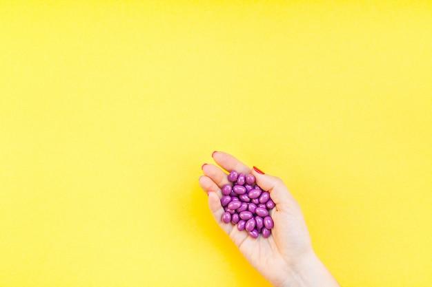 Main de femme tenant une poignée de pilules violettes