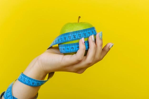 Main de femme tenant une pomme fraîche avec un ruban à mesurer.