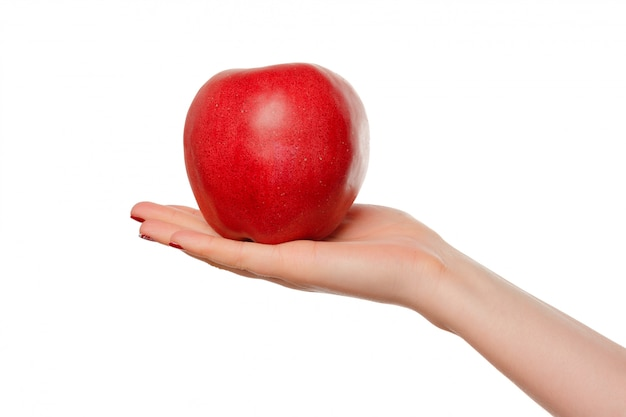 Main de femme tenant une pomme rouge.