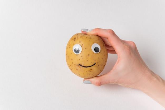 Main de femme tenant des pommes de terre crues avec grimace. pommes de terre aux yeux écarquillés et sourire sur fond blanc