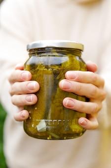 Main de femme tenant un pot de concombres marinés. préparation domestique marinage et mise en conserve de légumes