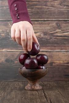 Main de femme tenant une prune violette dans un bol en bois.