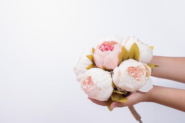 Main de femme tenant des roses de pivoine.
