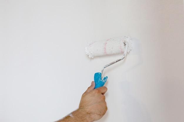 Main de femme tenant un rouleau à peinture isolé sur un mur blanc