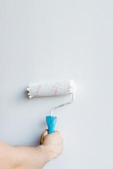 Main de femme tenant un rouleau à peinture isolé