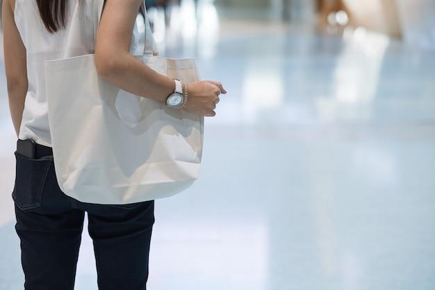 Main de femme tenant le sac eco shopping en magasin avec espace de copie pour le texte. protection de l'environnement, zéro déchet, réutilisable, ne dites pas de plastique, concept de la journée mondiale de l'environnement et du jour de la terre