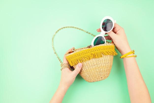 Main de femme tenant un sac de paille avec des accessoires de vacances d'été. vacances d'été, voyage dans les pays tropicaux, bord de mer, concept de style d'été. vue de dessus, pose à plat