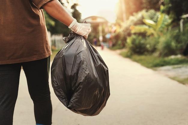 Main de femme tenant un sac poubelle pour le recyclage en mettant à la poubelle