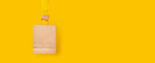 Main de femme tenant un sac à provisions en papier sur un mur jaune.