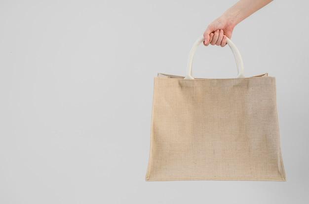 Main de femme tenant un sac à provisions en sac. pas de concept de sac en plastique