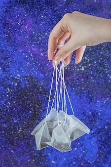 Main de femme tenant des sachets de thé sur un mur bleu.