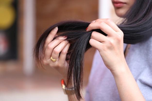 Main de femme tenant ses cheveux longs avec à la recherche de points de fractionnement endommagés des problèmes de soins capillaires