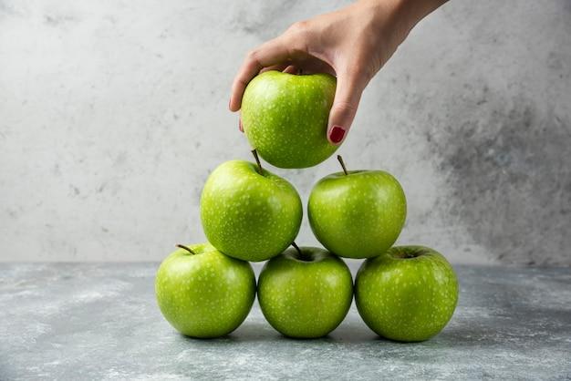 Main de femme tenant une seule pomme parmi beaucoup.