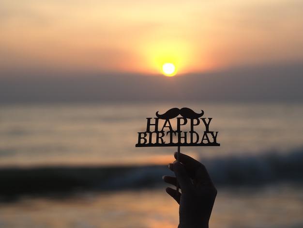 Main de femme tenant le signe de joyeux anniversaire sur fond de plage magnifique.