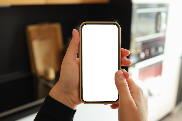 Main de femme tenant un smartphone avec écran blanc vertical dans la cuisine à la maison