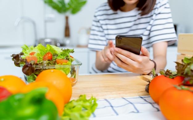 Main de femme tenant un smartphone et un saladier à la tomate et divers légumes à feuilles vertes sur la table à la maison, prenez votre publicité.