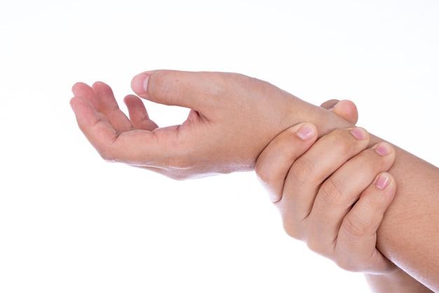 Main de femme tenant son poignet isolé mur blanc.