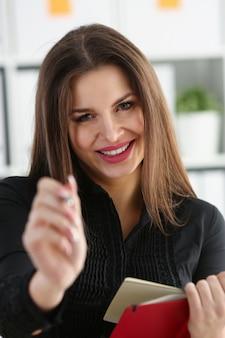 Main de femme tenant un stylo argenté prêt à faire